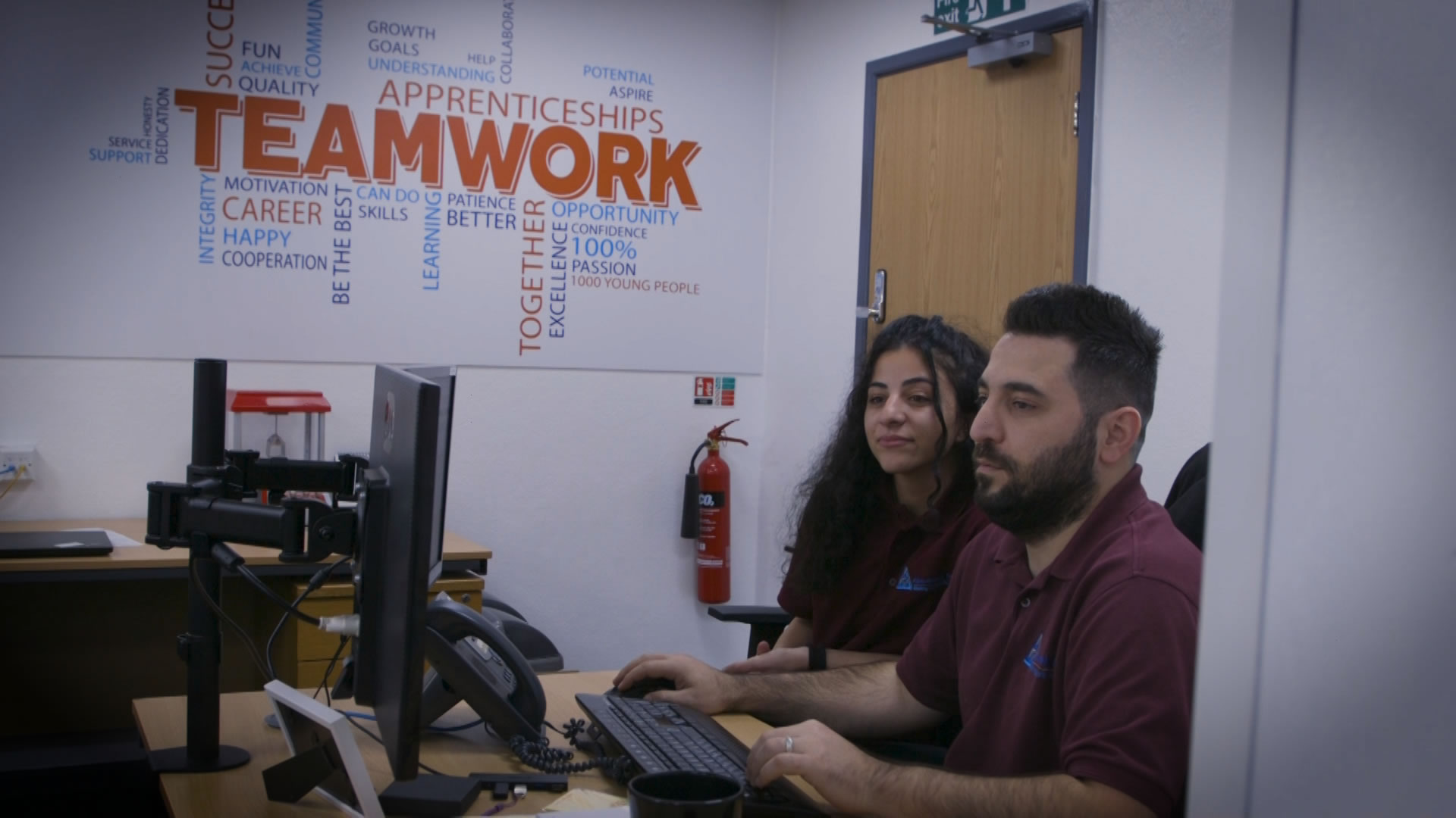 IT Technicians Working Next To Teamwork Sign